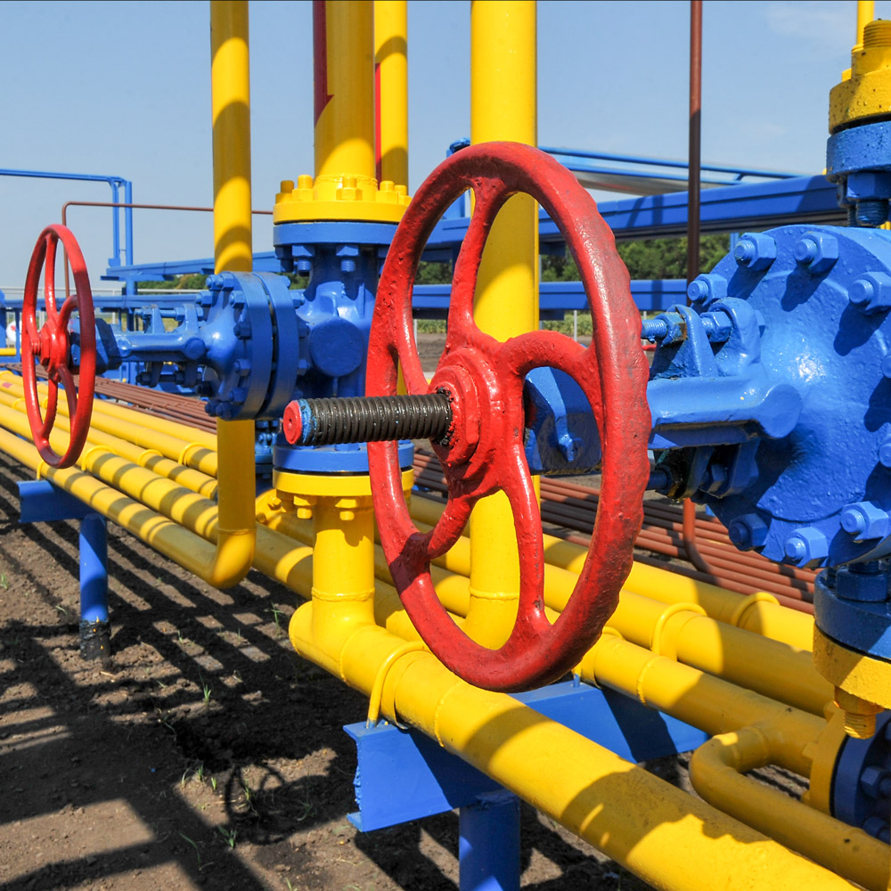 Red circular valve handles and steel pipe pump system coated in vibrant thermal spray paint coatings in natural gas treatment plant